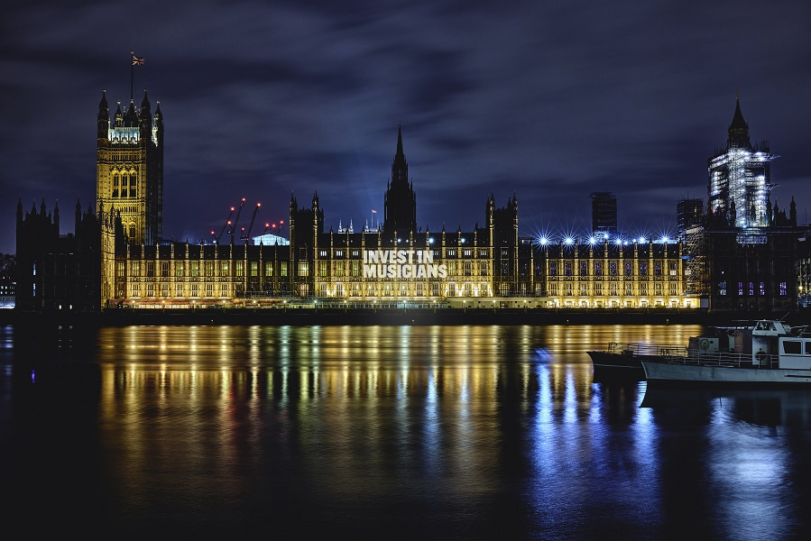 Photograph of the houses of parliament at night, with a light projection shone on it with the words