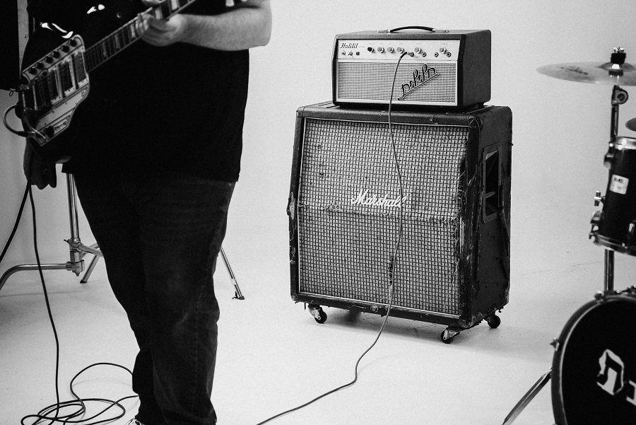 Black and white photo of a guitarist holding an electric guitar standing in front of a large amplifier