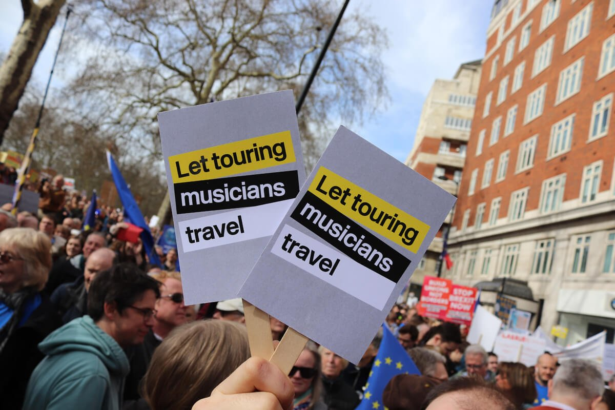 Someone holding the 'Let touring musicians travel' placards in the crowd