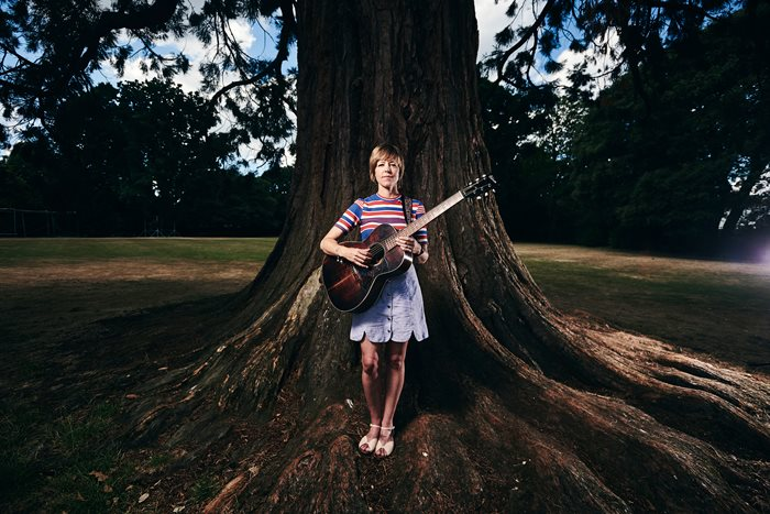 Emily Barker with a guitar standing against a bigtree