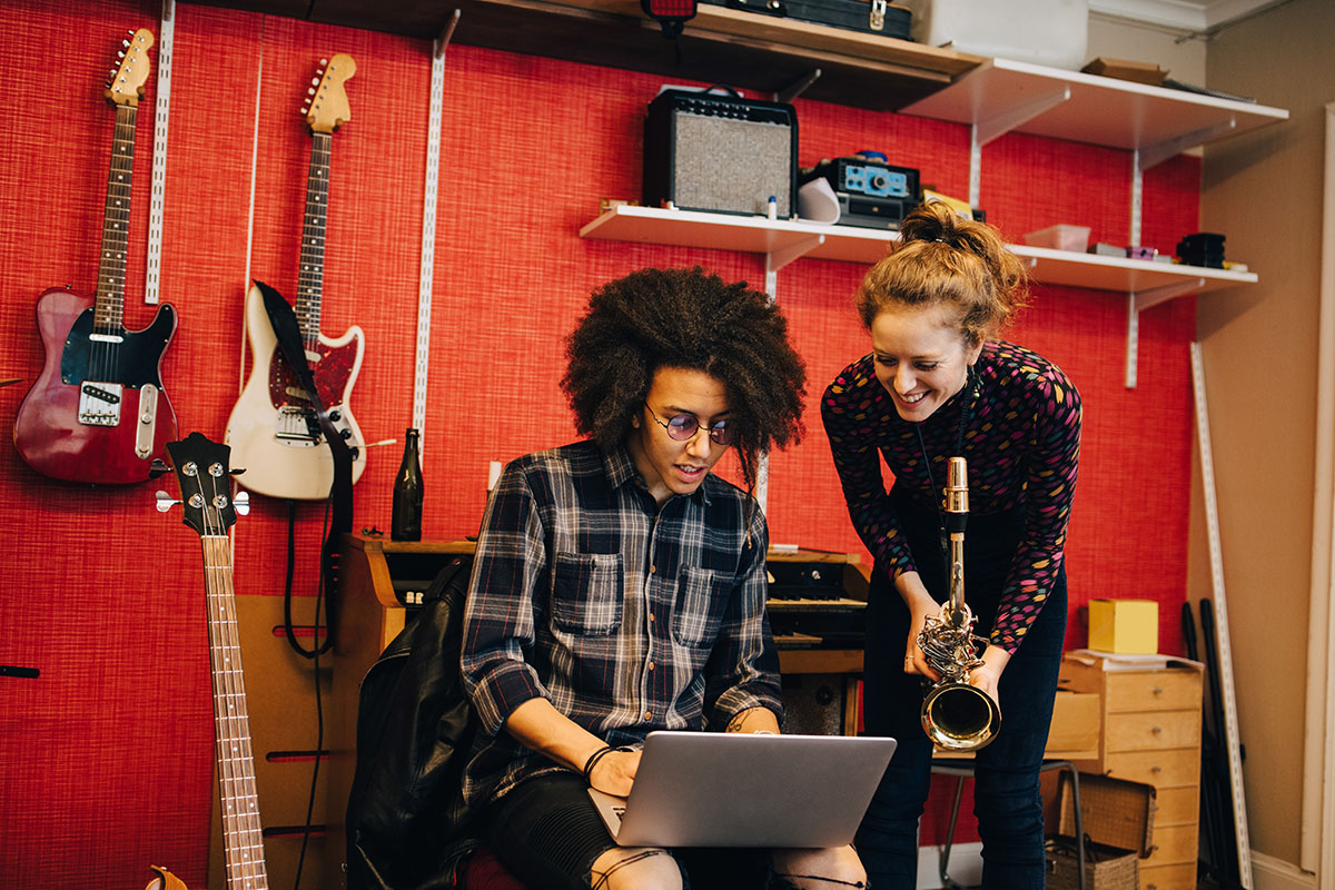 two musicians with a laptop in a music instrument shop