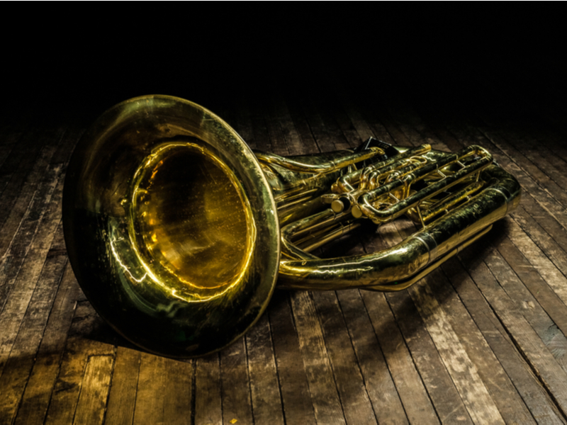 Golden euphonium lies on a brown wooden stage in the light of a spotlight