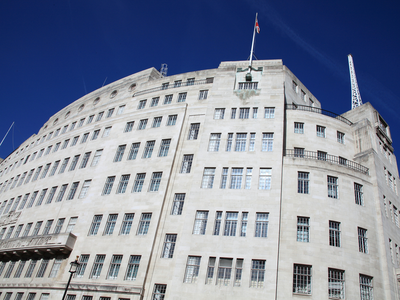 Photograph of the BBC Portland Place building, a large grey building with art decco features. The sky above is a bright blue.