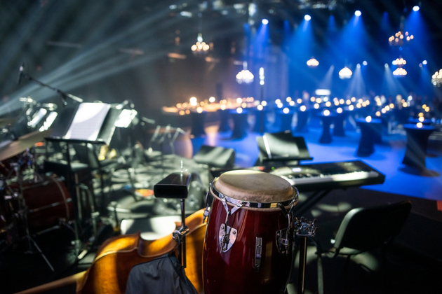 Photograph of what appears to be an empty theatre pit set up for musicians, with a drum, double bass and electronic keyboard set out.