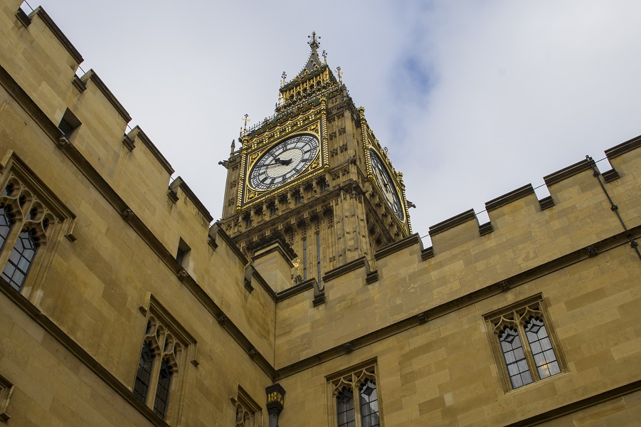 Photograph of Big Ben, a below photo showing just the clock face angled against a cloudy sky.