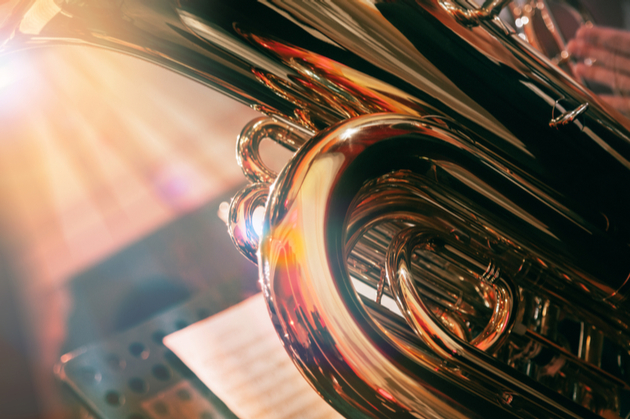 Photograph of a brass instrument being played in an orchestral context. We are close to the instrument, but can see music stands and more musicians blurred in the background.