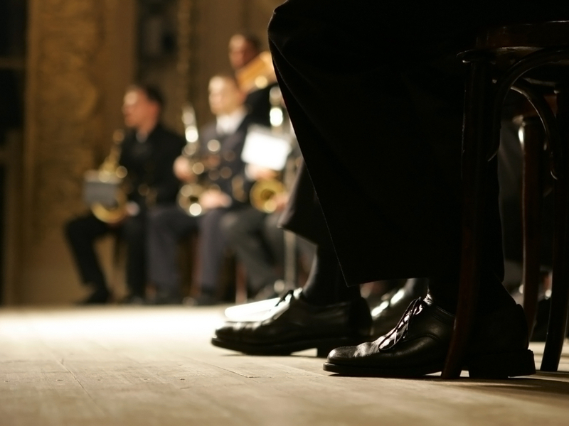 Photograph of a brass band ensemble, we can only see the feet of the closest musicians, with other musicians holding brass instruments slightly blurred in the background.