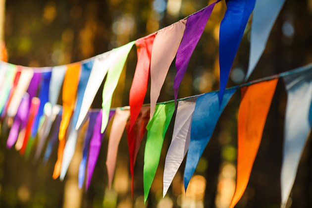 Photograph of colourful bunting hanging up in the sunshine.