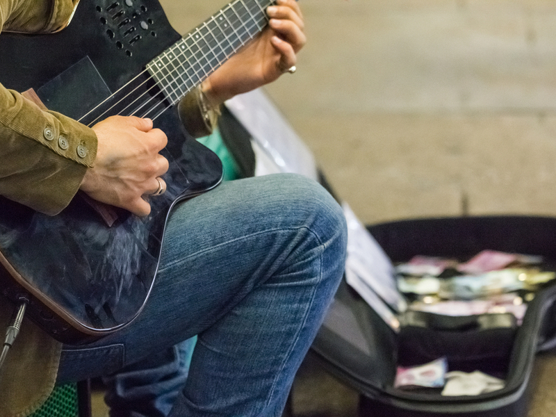 Photograph of a busker, their head isn't visible but they are wearing blue jeans and holding a plugged in electric guitar. In the background an open guitar case has money collected in it.