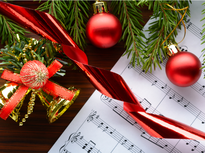 A photograph of some partly visible sheet music, with various Christmas decorations draped over it.