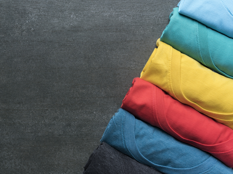 Photograph of a row of different brightly coloured t-shirts.