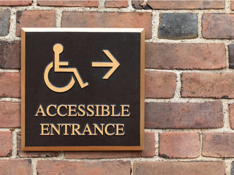 Photograph of an accessible entrance sign attached to a brick wall outside a building.