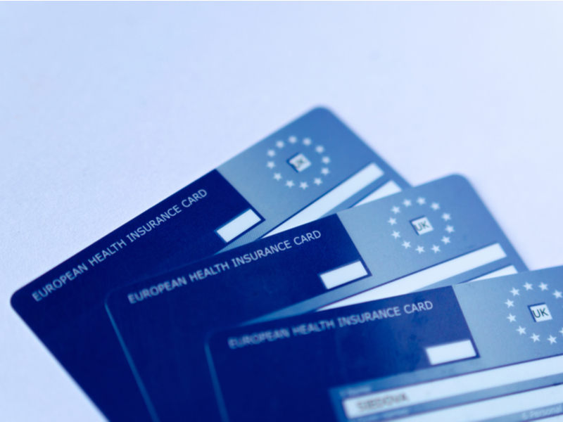Three of the familiar, blue plastic European Health Insurance Cards stacked against a pale blue background