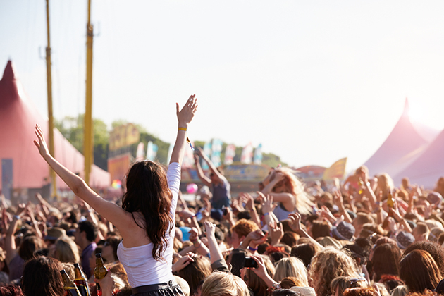 Photograph of a crowded festival audience, outdoors and the sun is shining.