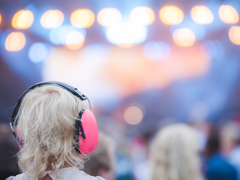 Photograph of a young girl wearing ear protectors at a concert. The background is blurred but we can see multiple people and string lights.