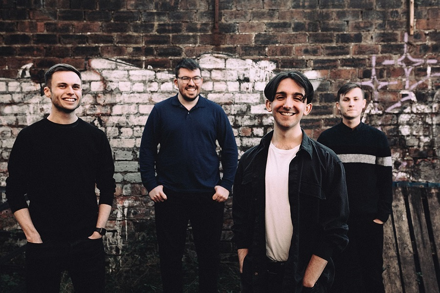 Photograph of the band Gnoss, they are four men standing in front of a brick wall. Hands in their pockets, they are smiling at the camera.