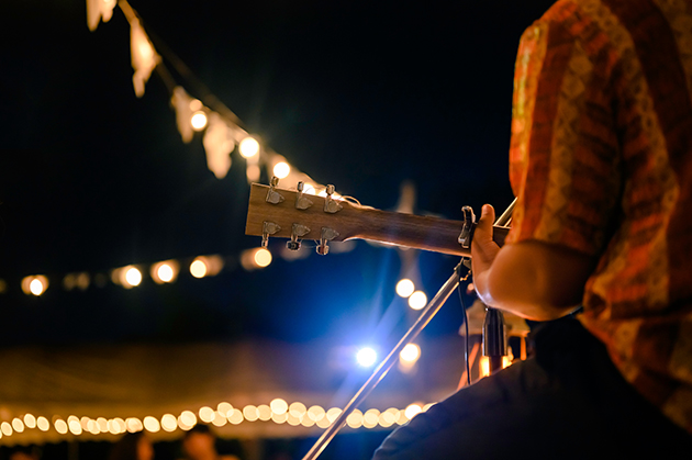 Photograph of an outdoor music performance taking place at night. We can only see the neck of a guitar and the shoulder of the musician, in the background there is bunting and bright lights.