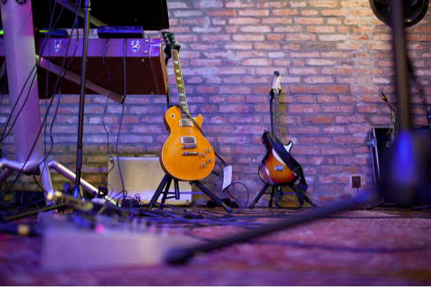 Photograph of a couple of guitars set back stage in an indoor venue