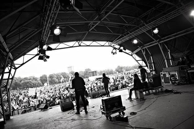 Black and white photograph from backstage at a festival. We can see a number of musicians playing on stage from behind, and a large outdoor audience facing inwards.