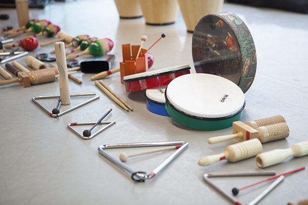 Photograph of an assortment of percussive instruments set out for use in a classroom.