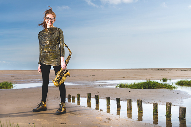 Jess Gillam with her saxophone on the beach