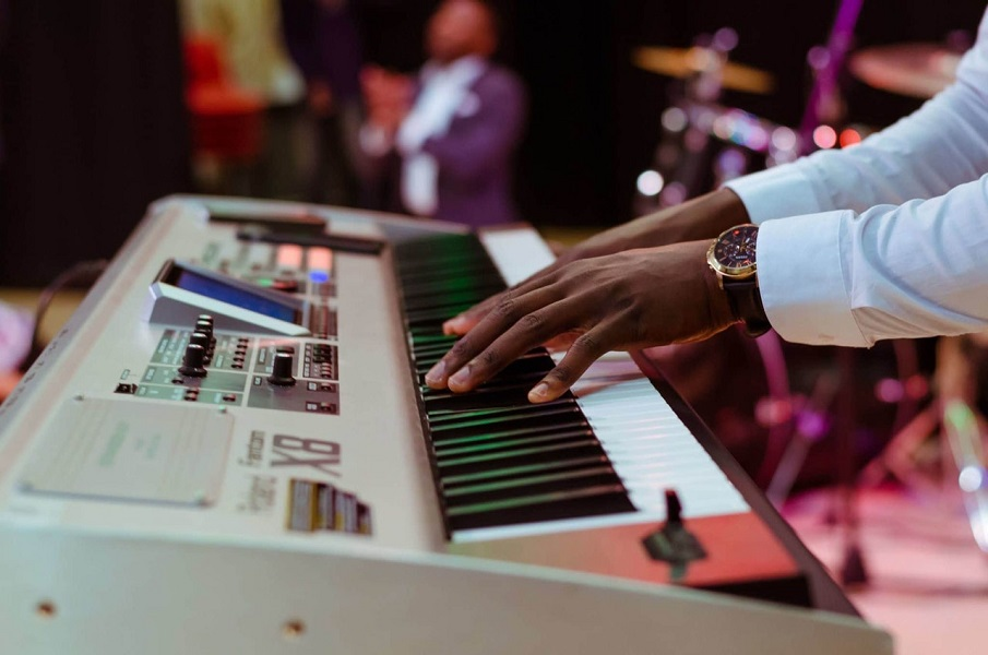Photograph of a young persons hands on an electric piano keyboard, the background is busy and lit in purple lights - there is a blurred band playing.