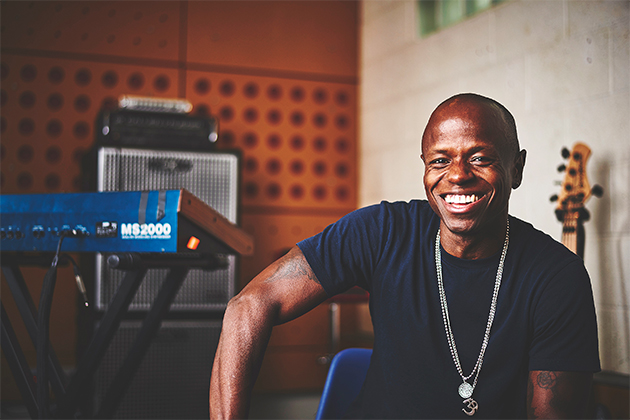 Kojo Samuel in his studio, smiling, sitting next to a guitar and a Korg MS2000 synth
