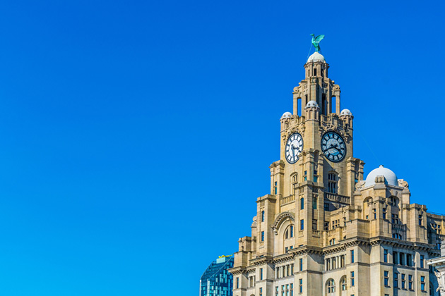 Photograph of the Liver building in Liverpool against a bright blue sky.