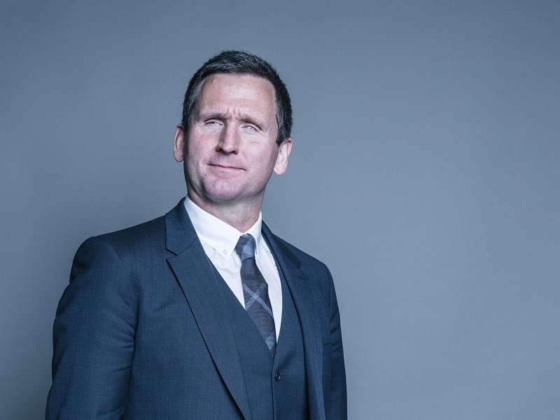 Portrait photograph of Lord Holmes, he wears a blue suit against a plain grey background and a serious expression.
