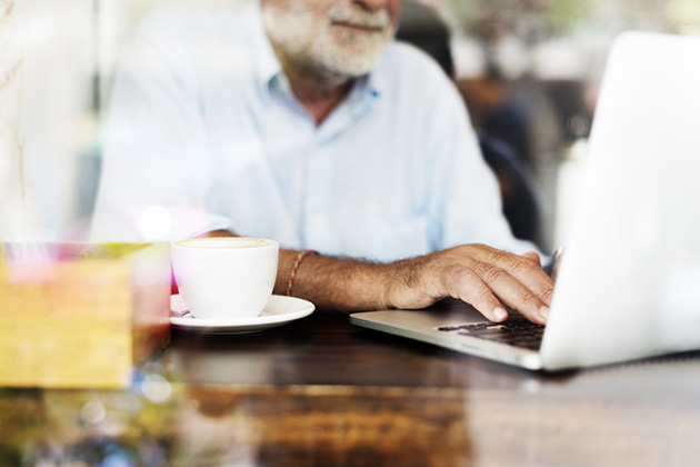 Photograph of a man working on a laptop next to a cup of coffee