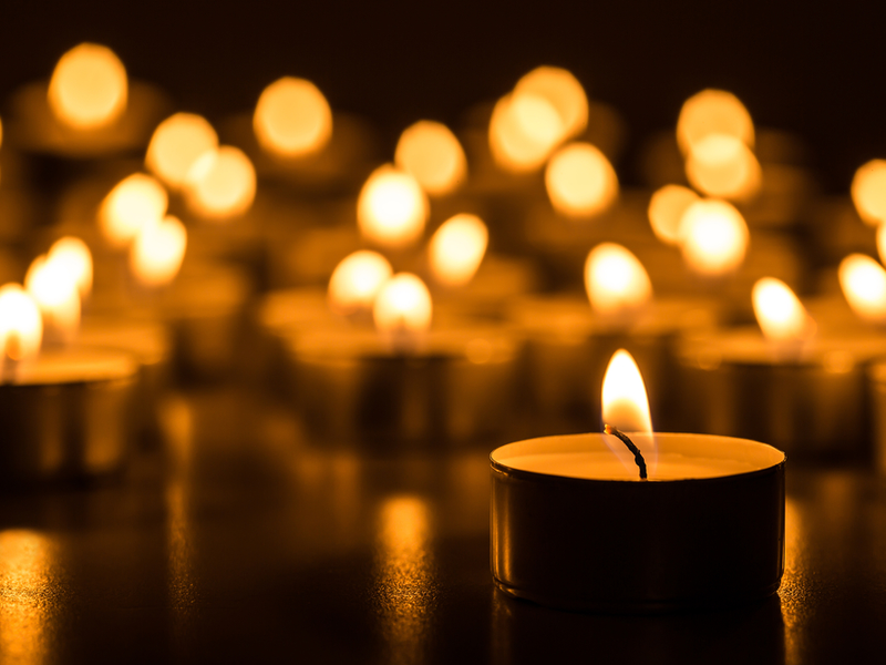 Photograph of multiple memorial candles burning with golden light against a dark background.