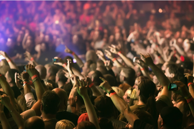 Photo of music audience crowd, hands raised towards off-shot performer