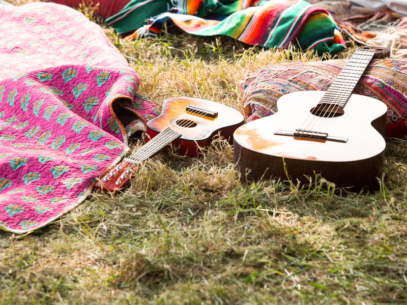 Two guitars resting in the grass amongst various objects like blankets and colourful pillows which indicate a festival campsite.