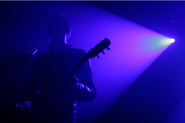Photograph of a musician playing a guitar, the heavy blue light means we can't clearly see the performer.