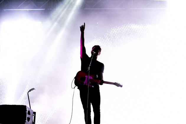 Musician silhouetted against a pale purple background, holding a guitar, one arm raised.