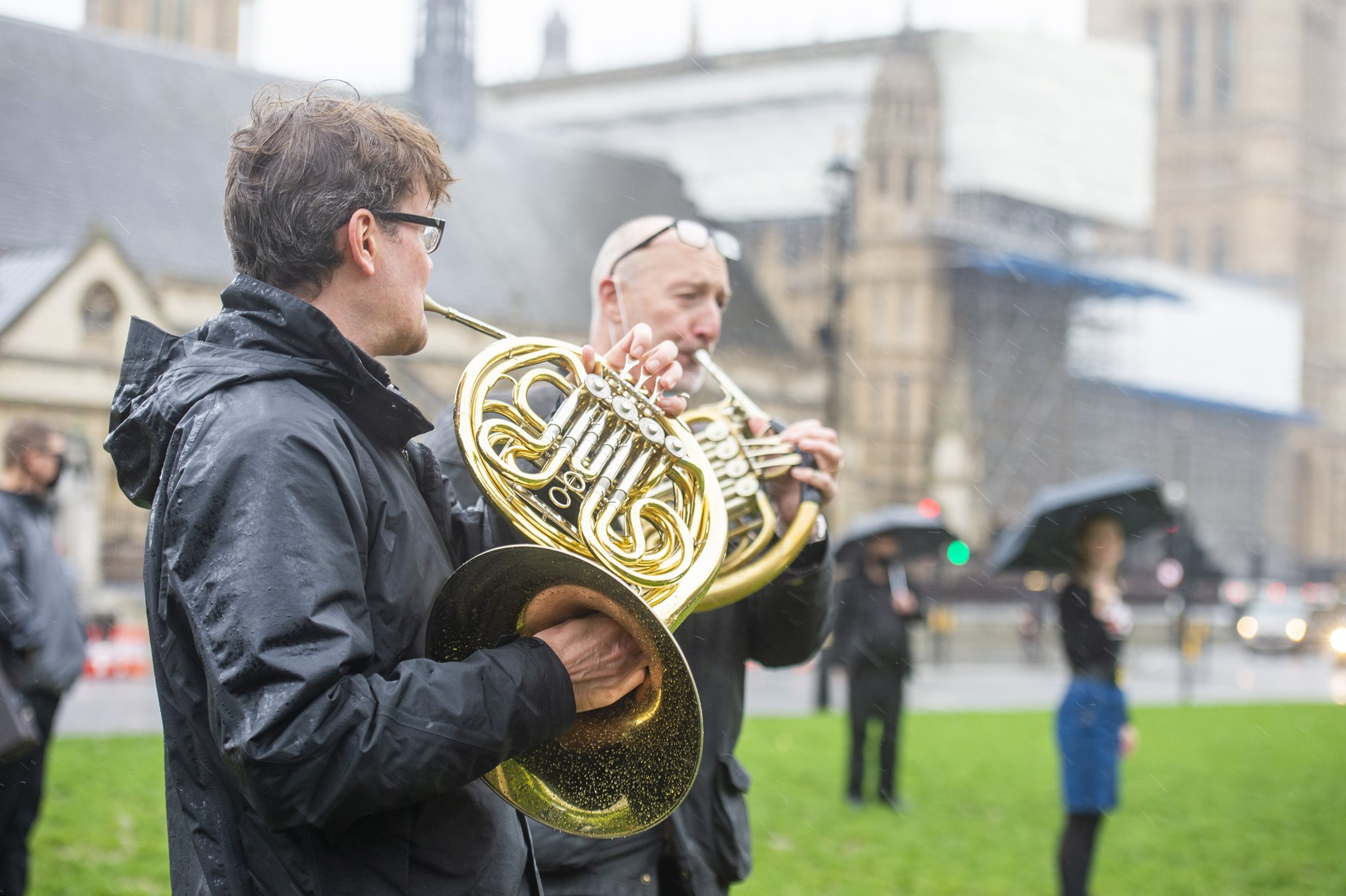 Photograph of a number of musicians playing brass instruments in the rain on Parliament Square.