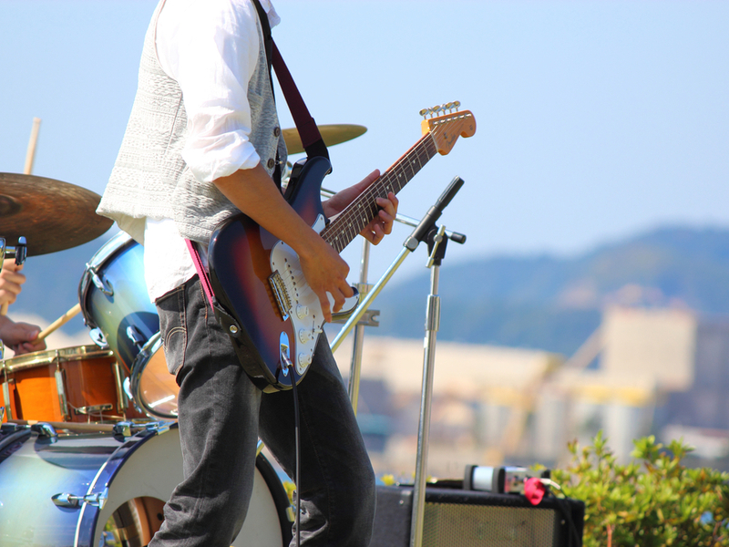 Photograph of a music event outdoors. The guitarist is gesturing dramatically from the stage with pick and electric guitar, and you can see a drum kit with a drummers hands behind.