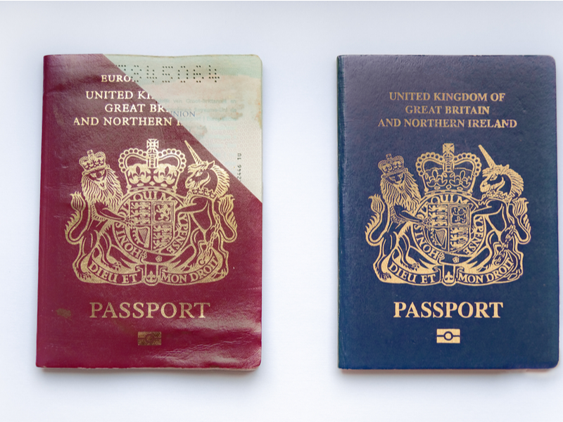 Two UK passports back to back, one is the old style EU red passport, the other is the newer blue passport.