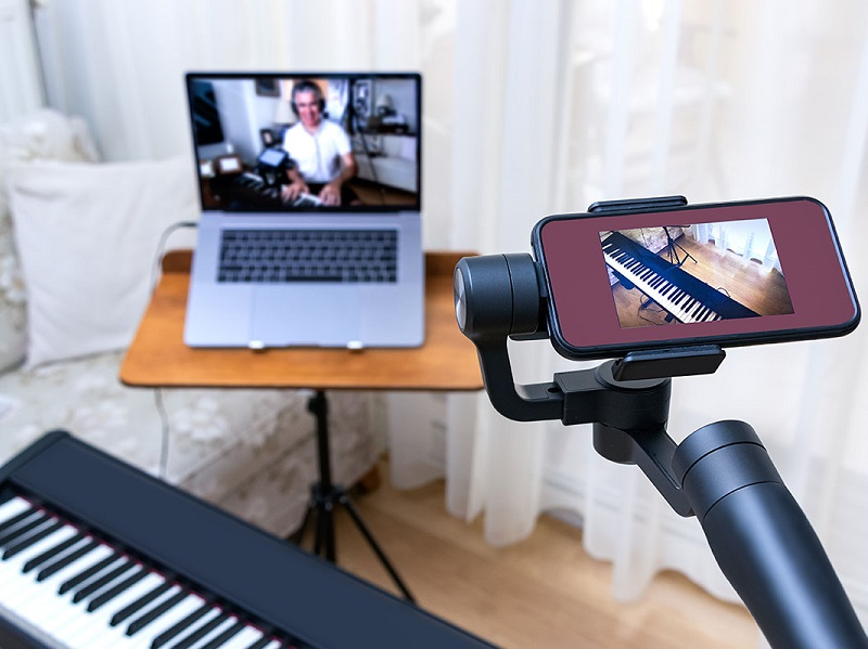 Photograph of an online teaching set up, a mobile phone camera and a laptop camera are recording a person playing on a keyboard.