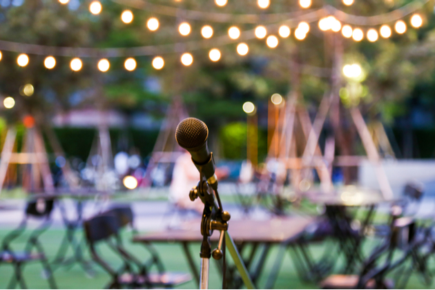 Set up for an outdoor concert, there are lights and a microphone is set up with tables and chairs in the background.