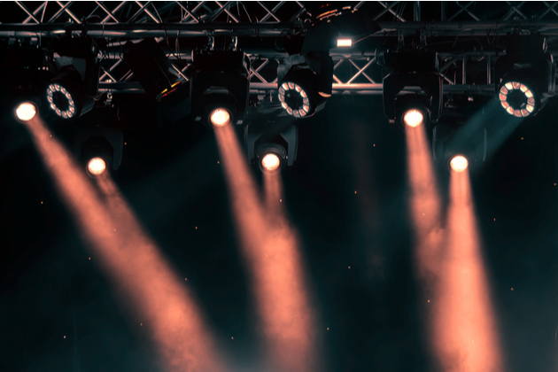 Photograph of pink stage lights beaming down into the darkness. The picture focuses upwards, so we can just see the lights and rigging and not the stage.