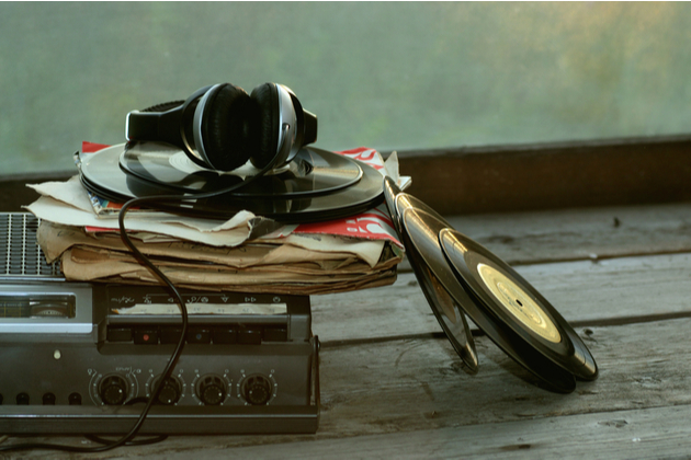 Photograph of a stack of records piled on top of a playing device, with earphones.