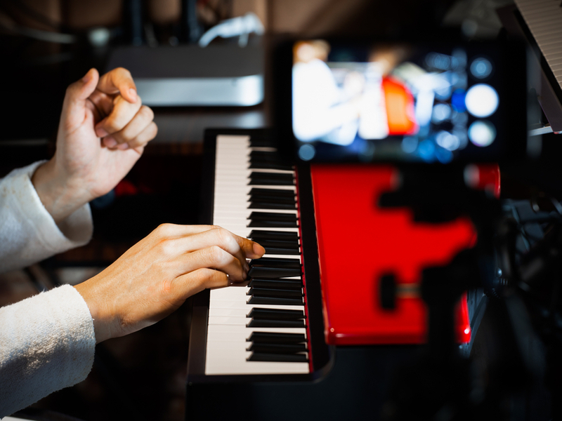 Photograph of a musician recording themselves playing on a piano with a webcam on video mode zoomed in on their hands.