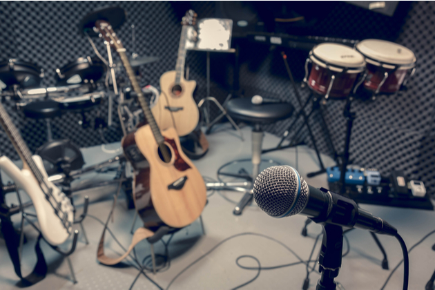 Photograph of a number of instruments, including an acoustic guitar and percussion, propped around a recording studio with various microphones.