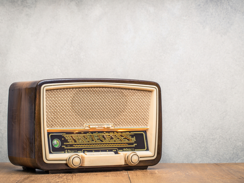 A photograph of a retro looking radio against a grey background.