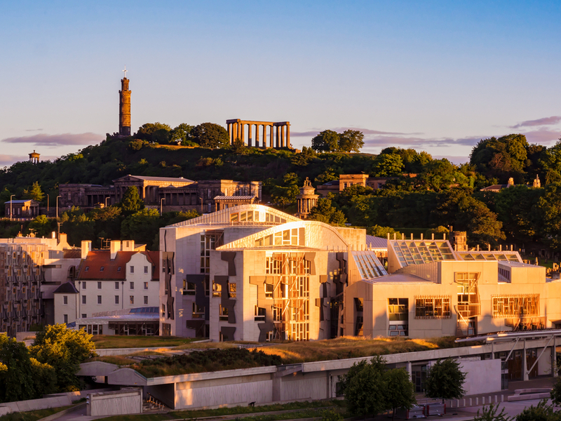 The sun is setting over the Scottish Parliament buildings as they stand in Holyrood, Edinburgh.