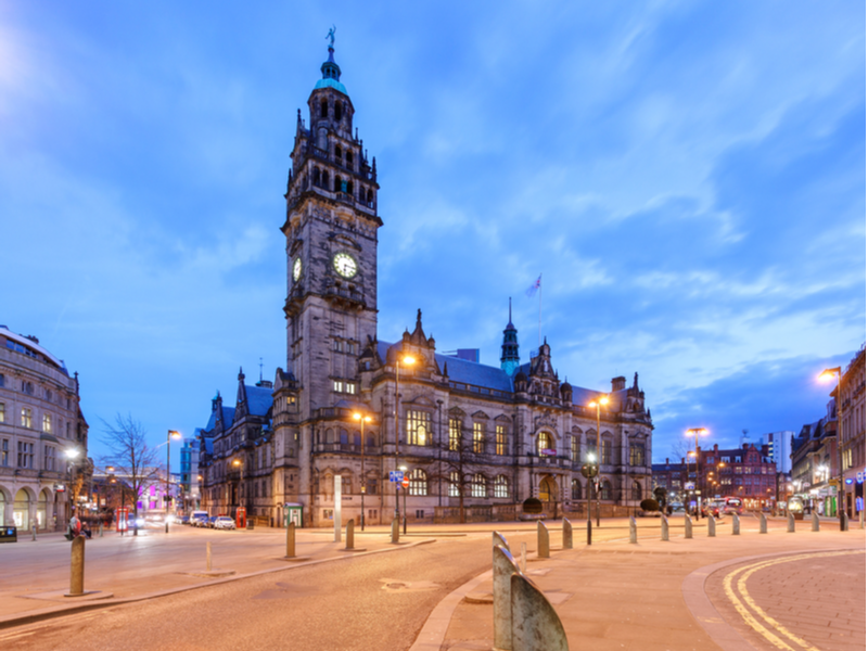 Photograph of Sheffield town hall, taken at dusk the sky is darkening and the street lights have just turned on.