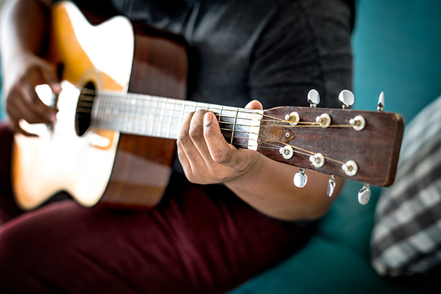 Photograph of a musician holding a guitar, we can't see their face and the photo focuses on their hands on the fretboard.