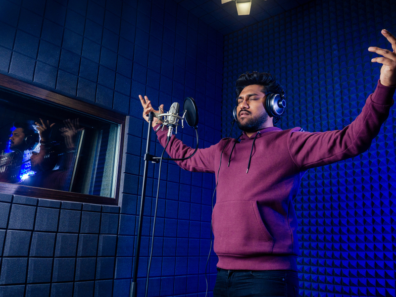 Man engrossed in singing into a microphone in a recording studio, he is dressed casually in a hooded jumper and has his arms raised and eyes closed in concentration.