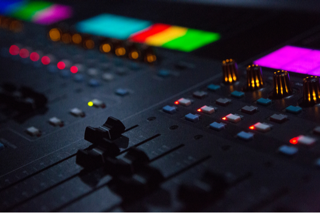 Photograph of a mixing desk with brightly coloured lights. Photo credit: Shutterstock